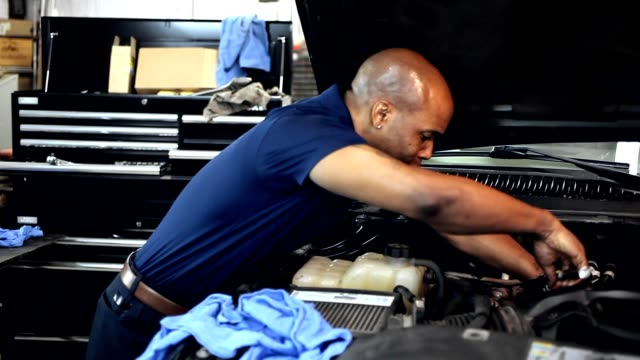 Male mechanic working in auto repair shop. video