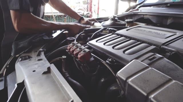 Hombre mecánico trabajando en taller de reparación de automóviles. - vídeo