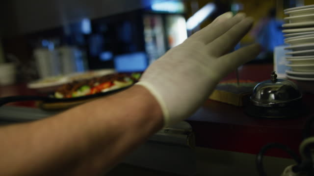 male mexican cook in his thirties places a steaming plate of fajitas in a serving window and rings a bell at a mexican restaurant - mestiere nella ristorazione video stock e b–roll