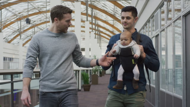 Male mixed-race couple walking indoors with their infant video