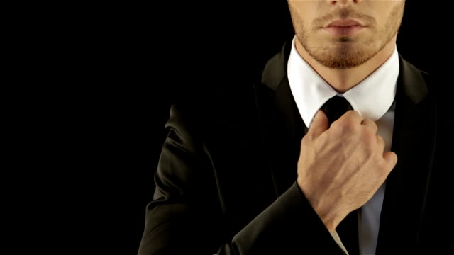Male model in stylish suite corrects his necktie video