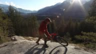 istock Male mountain biker relaxes on rock slab at sunrise 1134995201