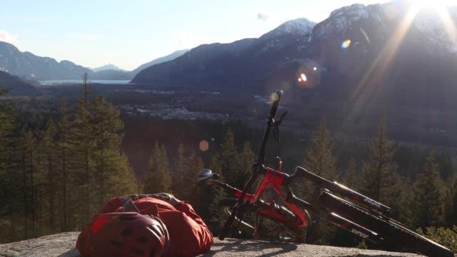 vidéos et rushes de motard de montagne mâle se détend sur la dalle de roche au lever du soleil - allongé sur le dos