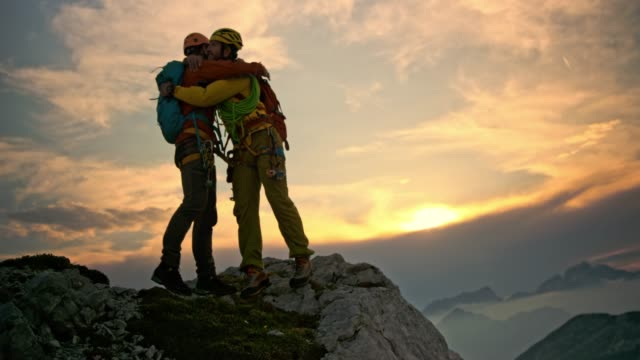 vídeos de stock e filmes b-roll de male mountaineer extending his hand and helping friend get to the mountain top at sunset - together