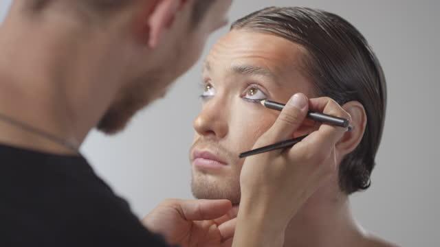 stockvideo's en b-roll-footage met mannelijke mua die zwarte eyeliner toepast op knappe mens - eyeliner