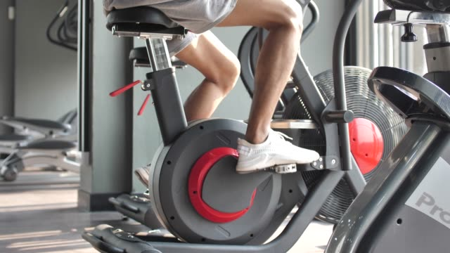 Male muscular exercising on a exercise bike in gym Male muscular exercising on a exercise bike in gym exercise bike stock videos & royalty-free footage