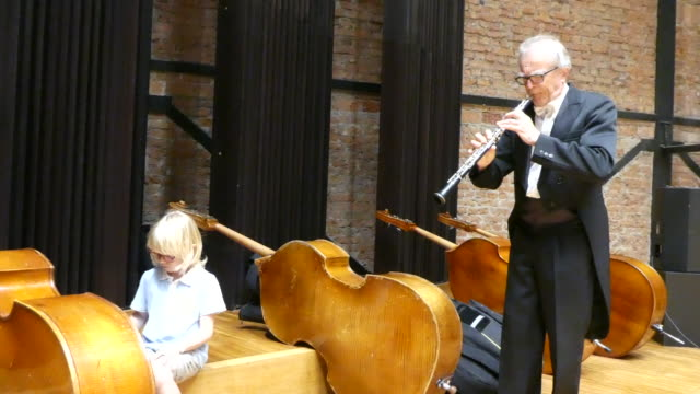 Male musician is having fun with his grandson playing an oboe and double bass.