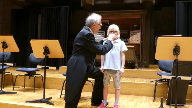 Male musician teaching cute boy how to play.
