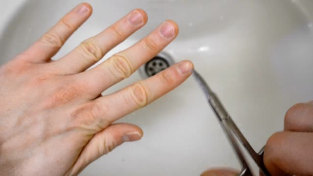 male nail grooming with scissors on finger over sink or wash basin in the morning - pedicure filmów i materiałów b-roll
