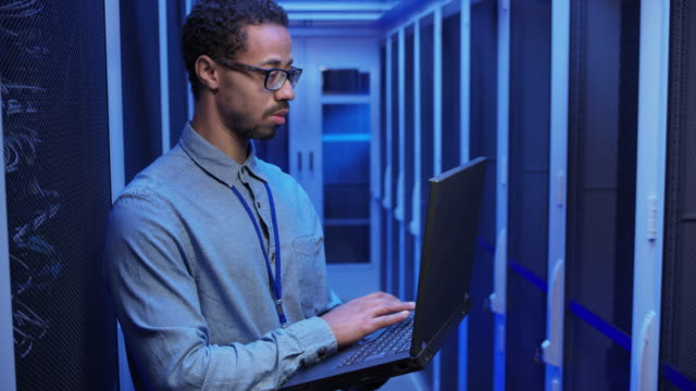 Male network engineer doing a system check standing in the server room with his laptop