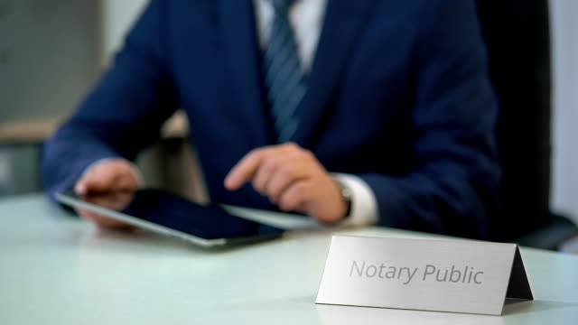 Male notary public viewing files on tablet, checking documents for notarization - vídeo