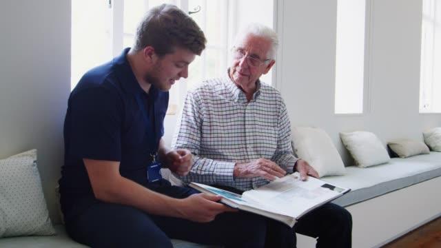 vídeos y material grabado en eventos de stock de enfermero y senior hombre mirando un álbum de fotos juntos - memorial day