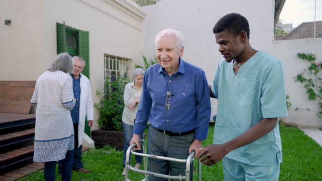 Male nurse assisting senior man with mobility walker in nursing home Male nurse assisting senior man with mobility walker in nursing home orthopedic equipment stock videos & royalty-free footage