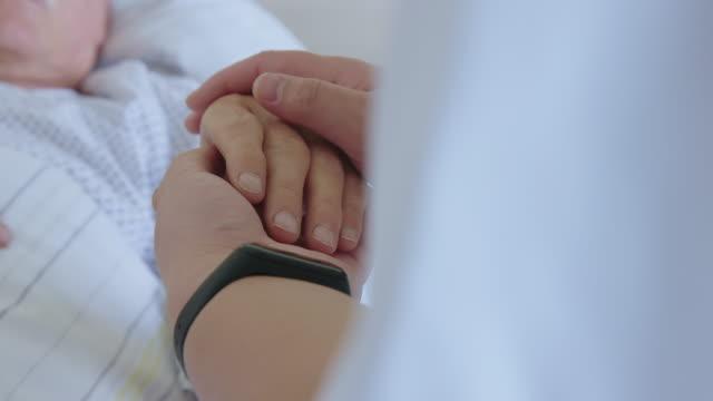 vidéos et rushes de homme hospitalisé de confort d'infirmière de femme dans le lit - infirmier