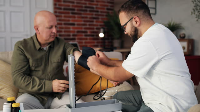 Male nurse doctor measures high low blood pressure check an elderly middle-aged man suffering from hypertension using a medical digital electronic tonometer at home, elderly people cardiology health video