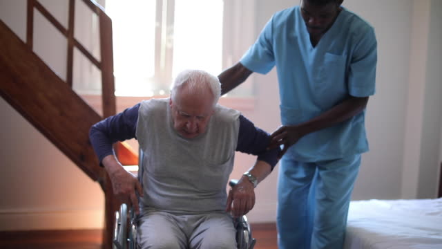 Male nurse helping an old man in nursery home  in the wheelchair Male nurse helping an old man in nursery home to get up and to sit and in the wheelchair pushing wheelchair stock videos & royalty-free footage