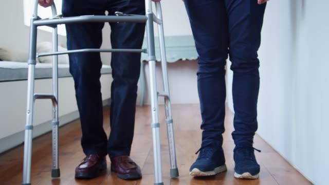 male nurse helping senior man use walking frame, low section - senior care stock videos and b-roll footage