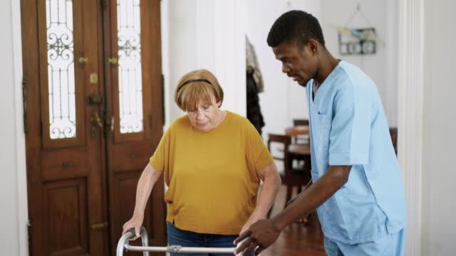 vídeos y material grabado en eventos de stock de enfermera masculina ayudando a la mujer mayor con movilidad caminante en el hogar de ancianos - geriatría