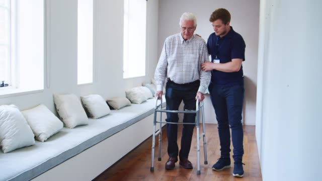 male nurse helps senior man using walking frame, full length - senior care stock videos and b-roll footage