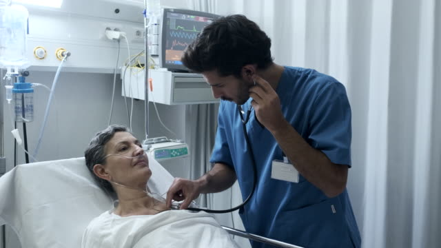 A male nurse is listening with a stethoscope a patient's chest Hospital lifestyle candid footage made in a real location in Barcelona. nhs stock videos & royalty-free footage