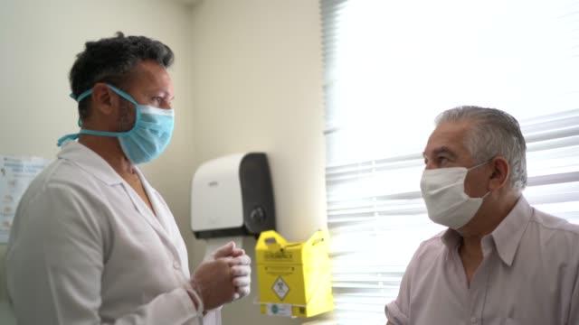 vídeos y material grabado en eventos de stock de enfermera masculina hablando con un paciente, preparándose para la vacunación - flu shot