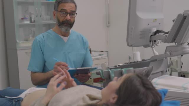 male nurse talking with pregnant woman before ultrasound examination. - femminilità video stock e b–roll