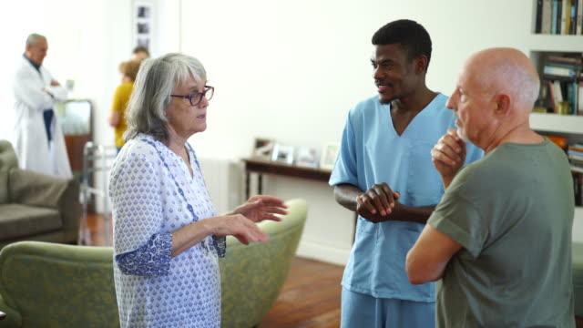 vidéos et rushes de infirmière mâle parlant avec deux patients aînés - infirmier