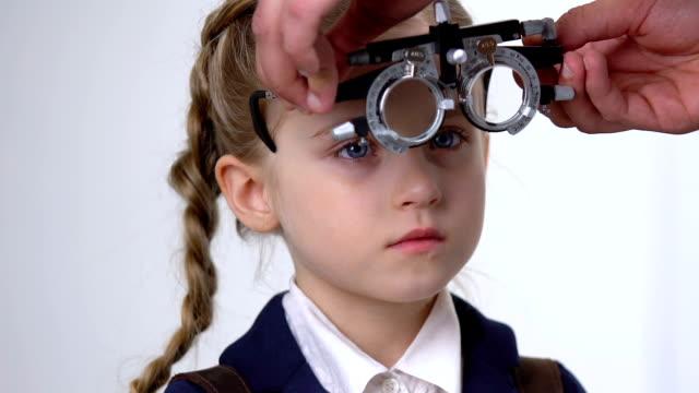 männliche okulistische überprüfung schulmädchen vision, lächelnde kind trägt phoropter, medizin - ophthalmologe stock-videos und b-roll-filmmaterial