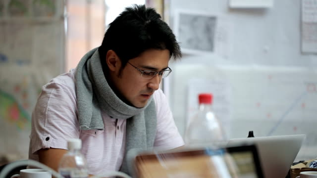 vídeos de stock e filmes b-roll de male of asian appearance cartographer in glasses and scarf working on the laptop - cartografia