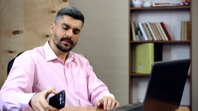 Male office worker getting a phone call from boss, giving updates about project video