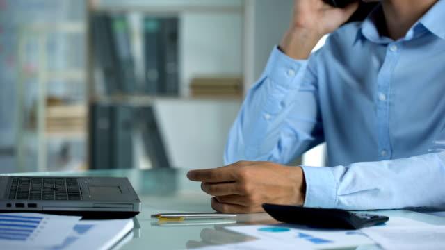 mężczyzna pracownik biurowy rozmawia przez telefon, wyznacza spotkanie z klientem, zawód - praca w sektorze handlowym filmów i materiałów b-roll