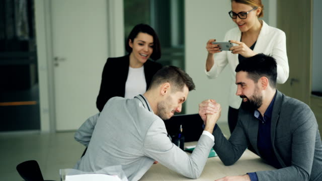 Male office workers are having fun doing arm-wrestling while girls are recording competition using smartphone and cheering guys. Work break and youth concept. video