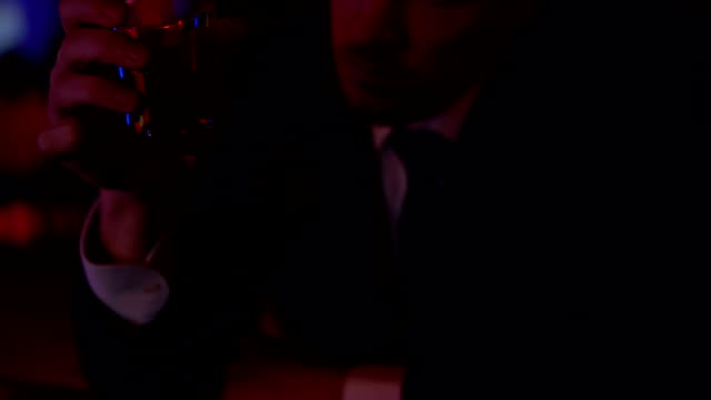 Male official thinking over business solution, drinking in bar alone, closeup video