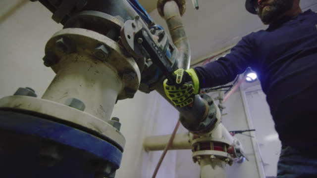 A Male Oilfield Worker in His Forties Opens/Closes Valves to Change the Pressure of Mud Flow in a Pump Room at an Oil and Gas Drilling Pad Site