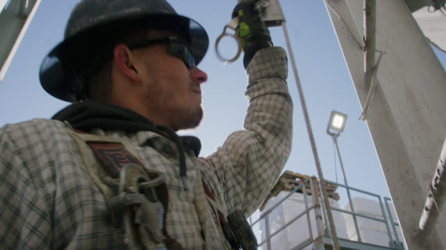 A Male Oilfield Worker in His Twenties Checks the Safety Cable on a Ladder on the Side of a Mud Tank at an Oil and Gas Drilling Pad Site on a Sunny Morning
