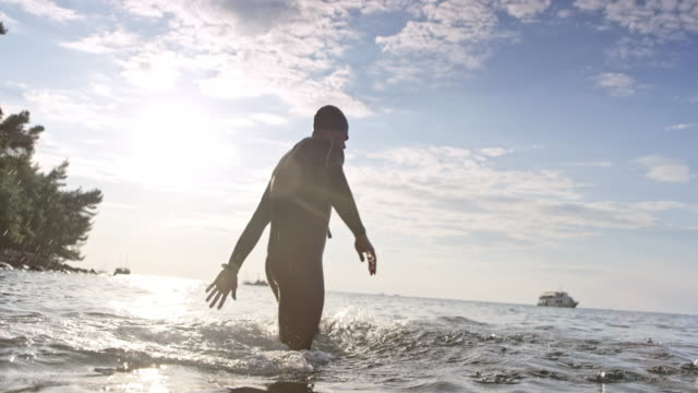 SLO MO Male open water swimmer staring from the beach in sunshine