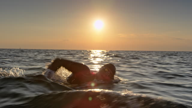 TS Male open water swimmer swimming forward crawl at sunset Wide tracking shot of a male open water swimmer swimming forward crawl in the sea at sunset. Shot in Slovenia. swimming stock videos & royalty-free footage