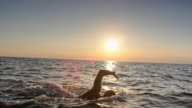 istock SLO MO TS Male open water swimmer swimming front crawl at sunset 1031154254