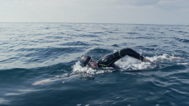 TS Male open water swimmer swimming front crawl in the sea Wide tracking shot of a male open water swimmer swimming forward crawl at sea. Shot in Slovenia. swimming stock videos & royalty-free footage