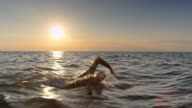 istock TS Male open water swimmer swimming in choppy sea at sunset 1031106068
