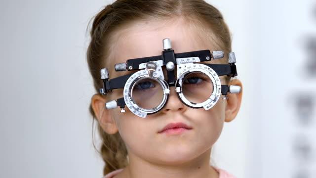 vidéos et rushes de ophtalmologiste mâle choisissant la lentille de lunettes pour la petite fille utilisant le phoropter - réfracteur