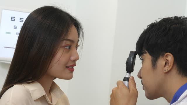 vidéos et rushes de optométriste mâle examinant l'oeil d'un patient féminin par l'outil d'essai - réfracteur