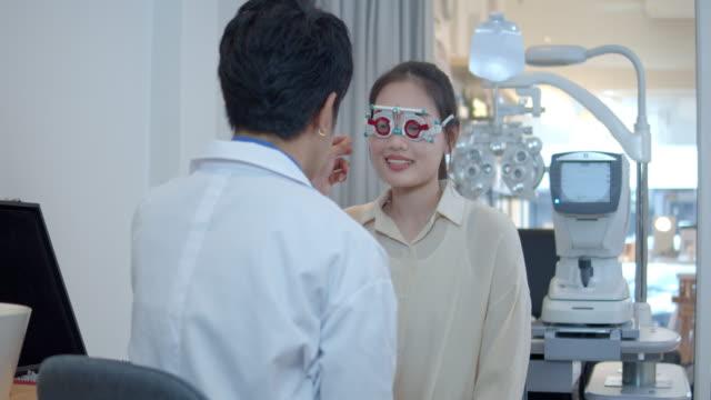 vidéos et rushes de optométriste mâle examinant la vue de femmes utilisant le cadre optique d'essai - réfracteur