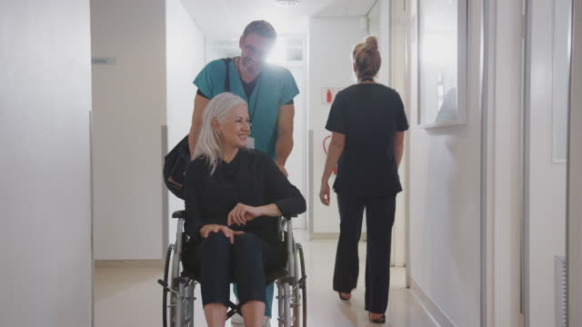 Male Orderly Pushing Senior Female Patient Being Discharged From Hospital In Wheelchair Male orderly pushing senior female patient being discharged along busy hospital corridor - shot in slow motion pushing wheelchair stock videos & royalty-free footage