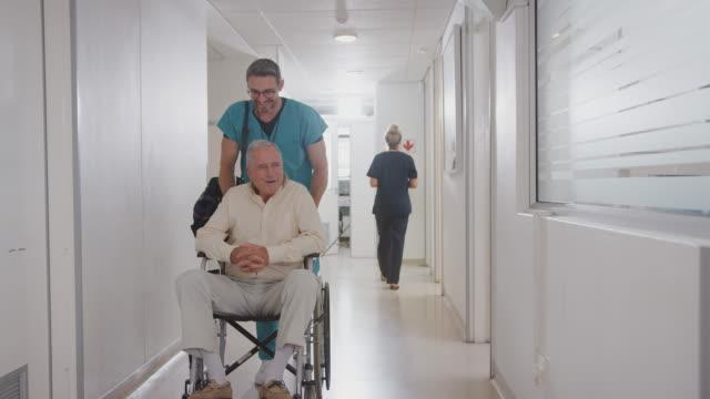 vídeos y material grabado en eventos de stock de hombre ordenante empujando al paciente varón mayor siendo dado de alta del hospital en silla de ruedas - despedida