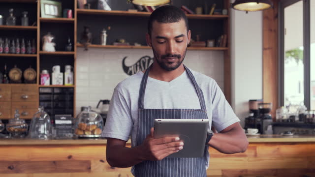 Male owner at his coffee shop using digital tablet Young african cafe entrepreneur standing against the counter using a digital tablet smiling and looking at camera wait staff stock videos & royalty-free footage