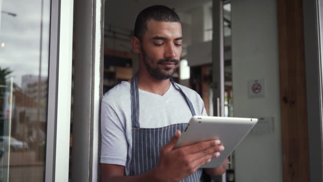 Male owner standing at the cafe entrance using digital tablet