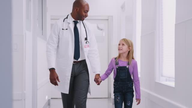 vídeos y material grabado en eventos de stock de médico pediátrico masculino dando joven paciente paciente alto cinco en el corredor del hospital - pediatra