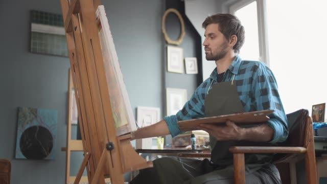 vídeos de stock e filmes b-roll de male painting on molbert in studio - trabalho de design