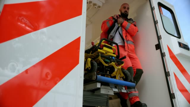 SLO MO DS Male paramedic carrying his paramedic bag and rushing out of the ambulance vehicle